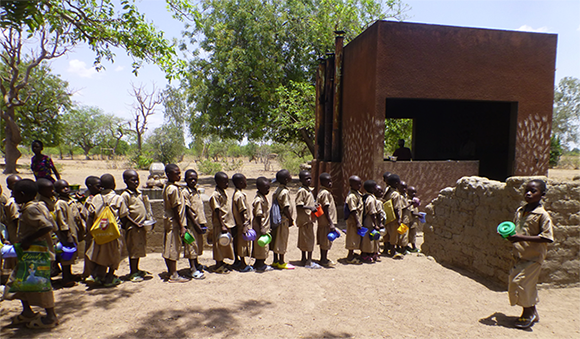 Primary school children lining up for lunch at the school kitchen.