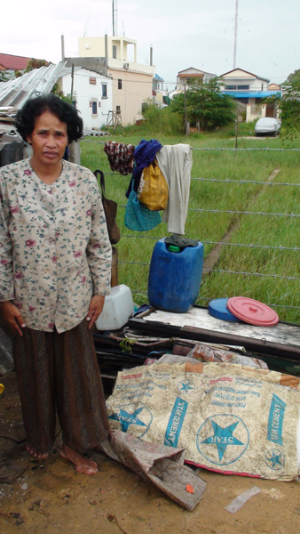 Mother of Srey Peou sows together garbage bags that are used by dumpsite labourers to collect recyclable waste. She earns less than 2 dollars a day and her income is irregular.
