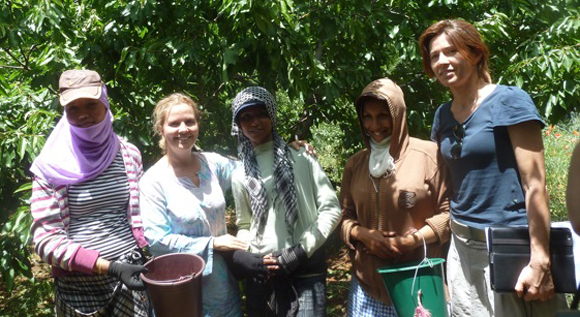 Students picking fruits on their day off school posing with volunteers Francesca Ferrari and Silvia Alfero