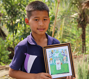 Nary holding his drawing that won an International Art Competition