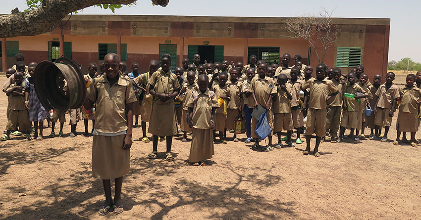 Nibagdo primary school. The girl in the foreground is sounding the school bell.
