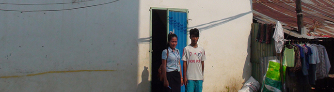 Thida posing with her brother in front of their home. They rent a room on the second floor where they live with their mother.